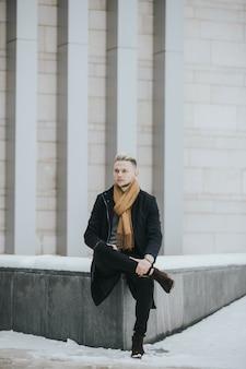 Vertikale aufnahme eines kaukasischen, stilvollen mannes, der im freien in einer verschneiten stadt posiert?
