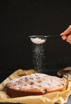 Vertikale aufnahme eines kirschkuchens mit zuckerpulver und zutaten auf der seite auf einem schwarzen hintergrund