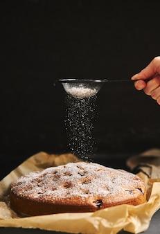 Vertikale aufnahme eines kirschkuchens mit zuckerpulver und zutaten auf der seite auf schwarz