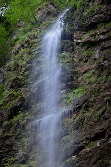 Vertikale aufnahme eines kleinen wasserfalls in den felsen der gemeinde skrad in kroatien