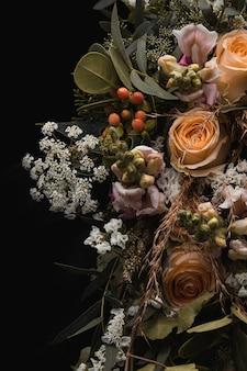 Vertikale aufnahme eines luxuriösen straußes von orangefarbenen rosen und weißen blumen auf einem schwarzen