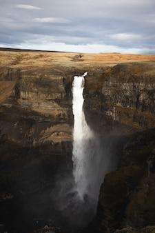 Vertikale aufnahme eines majestätischen hohen wasserfalls