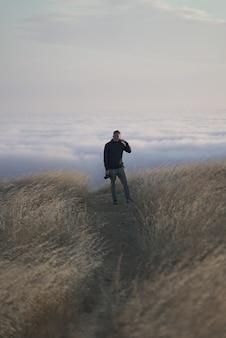 Vertikale aufnahme eines mannes, der die kamera oben auf dem berg betrachtet. tam in marin, ca.