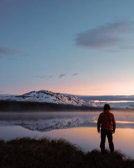 Vertikale aufnahme eines mannes, der vor einer schönen seelandschaft steht