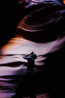 Vertikale aufnahme eines mannes mit einer kamera in einer höhle, die ein bild macht