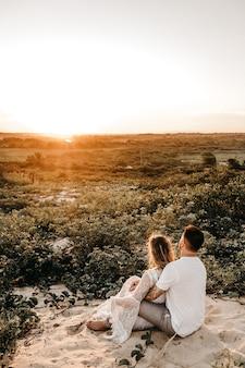 Vertikale aufnahme eines mannes und einer frau, die in einem feld sitzen und sich umarmen, während sie den sonnenuntergang betrachten