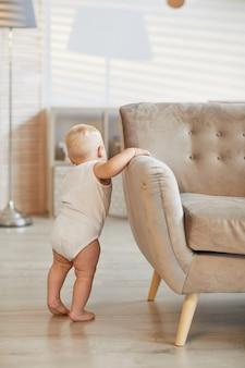 Vertikale aufnahme eines nicht erkennbaren kleinkindes, das auf dem sofa hält und lernt, auf seinen beinen zu stehen