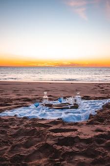 Vertikale aufnahme eines picknicks an der küste in der nähe des meeres unter einem sonnenuntergangshimmel