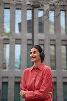 Vertikale aufnahme eines positiven dunkelhaarigen tausendjährigen mädchens hört musik in kopfhörern, während sie in der stadt spazieren geht, trägt ein rotes hemd, hält die arme verschränkt und sieht glücklich weg posiert in der nähe eines modernen gebäudes im freien