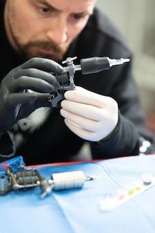 Vertikale aufnahme eines professionellen tätowierers, der eine tätowiermaschine zusammenbaut
