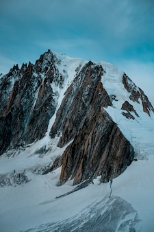 Vertikale aufnahme eines schneebedeckten berges mit einem blauen himmel