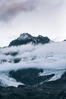 Vertikale aufnahme eines schneebedeckten berggipfels über den wolken mit einem klaren himmel