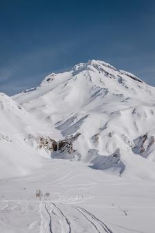 Vertikale aufnahme eines schönen schneebedeckten berges, der von einem steilen hügel mit blauem himmel im hintergrund geschossen wird