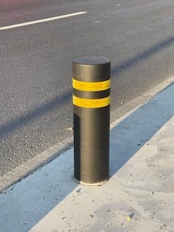 Vertikale aufnahme eines schwarzen straßenpollers mit gelben reflektierenden streifen bei sonnenuntergang