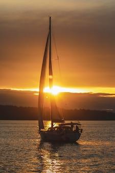Vertikale aufnahme eines segelboots im ozean während des sonnenuntergangs