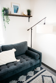 Vertikale aufnahme eines sofas und eines schönen entwurfs einer stehlampe im wohnzimmer