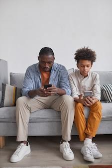 Vertikale aufnahme eines stilvollen afroamerikanischen teenagers, der zeit mit seinem vater zu hause auf dem sofa verbringt und videospiele auf smartphones spielt