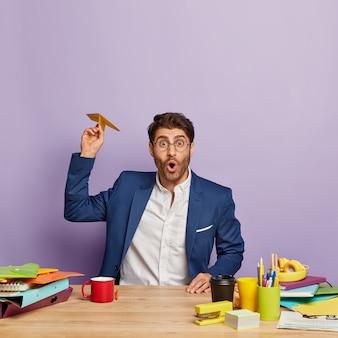 Vertikale aufnahme eines überraschten jungen männlichen unternehmers wirft papaer-flugzeug, hat das ziel, sein geschäft zu entwickeln, trägt formelle kleidung, sitzt am arbeitsplatz, trinkt kaffee, hat wenig chaos am arbeitsplatz