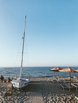 Vertikale aufnahme eines weißen segelboots am ufer in der nähe des wassers mit einem blauen himmel in der