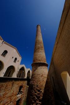 Vertikale aufnahme eines ziegelsteinturms nahe einer erwähnung an einem sonnigen tag