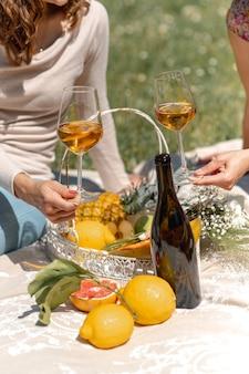 Vertikale aufnahme mit nicht erkennbaren frauen, die auf einer decke sitzen und picknick machen. frauen, die ein glas weißwein mit vielen tropischen früchten halten.