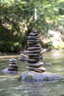 Vertikale aufnahme vieler steinpyramiden, die auf einem flusswasser balanciert sind