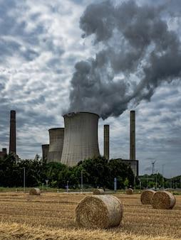 Vertikale aufnahme von aufsteigendem rauch, der die luft verschmutzt und heuschober im feld