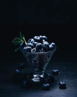 Vertikale aufnahme von blaubeeren in einem glas auf einer schwarzen wand