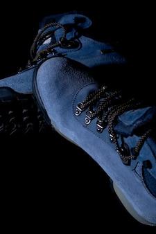 Vertikale aufnahme von blauen winterwanderstiefeln auf schwarzem hintergrund