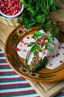 Vertikale aufnahme von chiles en nogada in einem teller auf einem holzbrett auf dem tisch