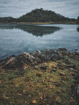 Vertikale aufnahme von felsen nahe dem wasser, das den berg reflektiert