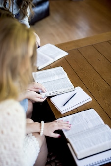 Vertikale aufnahme von frauen, die die bibel lesen und notizen machen