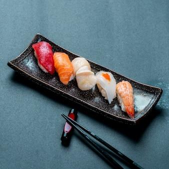 Vertikale aufnahme von frischem thunfisch, lachs, jakobsmuschel, nigiri und shrimps sushi und stäbchen
