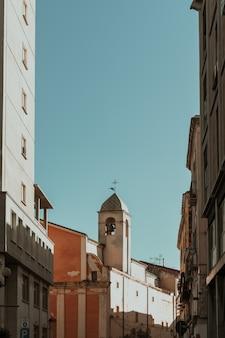 Vertikale aufnahme von gebäuden im glockenturm in der ferne und einem blauen himmel