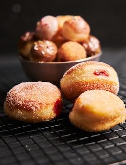 Vertikale aufnahme von gebratenen donuts mit zucker und sahne auf einem schwarzen tisch