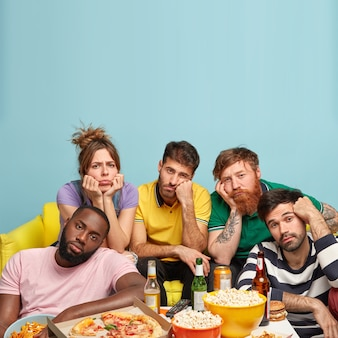 Vertikale aufnahme von gelangweilten kerlen, die langweilige sendungen im fernsehen sehen, freizeit zu hause verbringen, auf interessante filme warten, bier trinken und fast food essen. inländisches kinokonzept