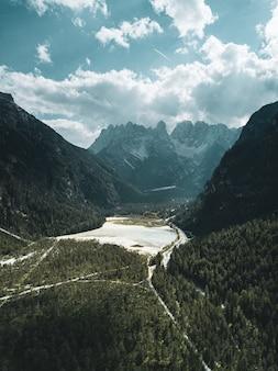 Vertikale aufnahme von grünen bergen mit weißen wolken am himmel