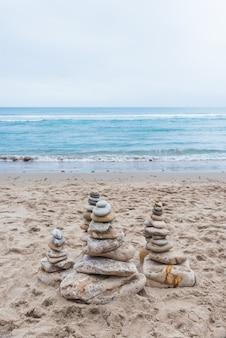 Vertikale aufnahme von kieselsteinen, die in einer balance am strand aufeinander gestapelt sind