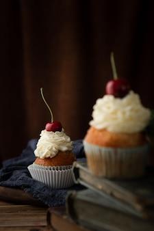 Vertikale aufnahme von köstlichen cupcakes mit sahne und kirschen an der spitze