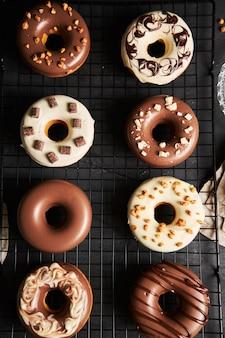 Vertikale aufnahme von köstlichen donuts bedeckt mit der weißen und braunen schokoladenglasur auf einem schwarzen tisch