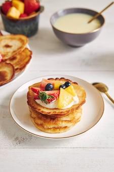 Vertikale aufnahme von köstlichen pfannkuchen mit früchten auf der oberseite beim frühstück