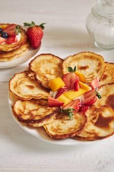 Vertikale aufnahme von köstlichen pfannkuchen mit früchten beim frühstück