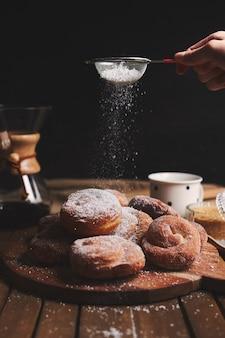 Vertikale aufnahme von köstlichen schlangenkrapfen, bestreut mit puderzucker und chemex-kaffee