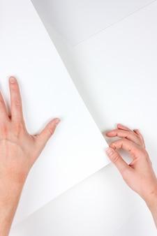 Vertikale aufnahme von menschlichen händen, die ein stück weißes papier mit einem weiß halten