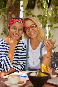 Vertikale aufnahme von multiethnischen frauen umarmen, sitzen zusammen im café