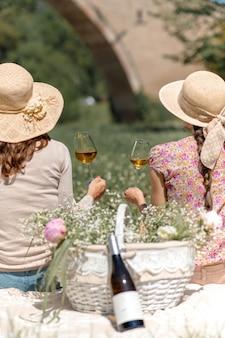 Vertikale aufnahme von nicht erkennbaren frauen, die einen strohhut halten, der auf einer decke in einem garten sitzt und weißweinglas hält.