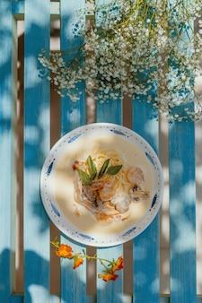 Vertikale aufnahme von pasta carbonara mit pilzen auf einer blauen holzbank