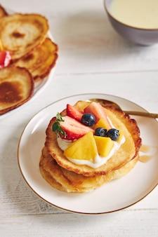 Vertikale aufnahme von pfannkuchen mit früchten auf der oberseite beim frühstück