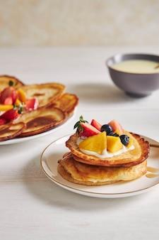 Vertikale aufnahme von pfannkuchen mit früchten auf der oberseite