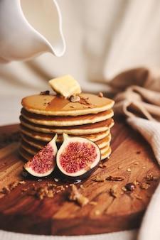Vertikale aufnahme von pfannkuchen mit sirup, butter, feigen und gerösteten nüssen auf einem holzteller